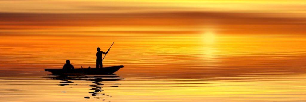 Bild für Blogbeitrag: Menschen auf einem kleinen Boot im Sonnenuntergang